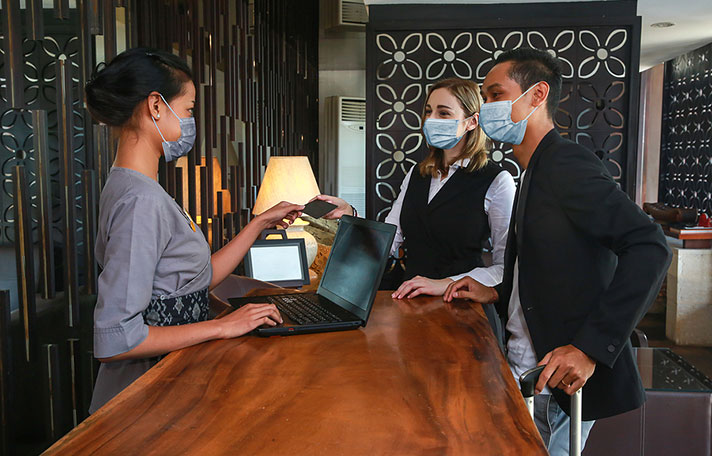 Couple and receptionist at counter in hotel wearing medical masks as precaution against coronavirus